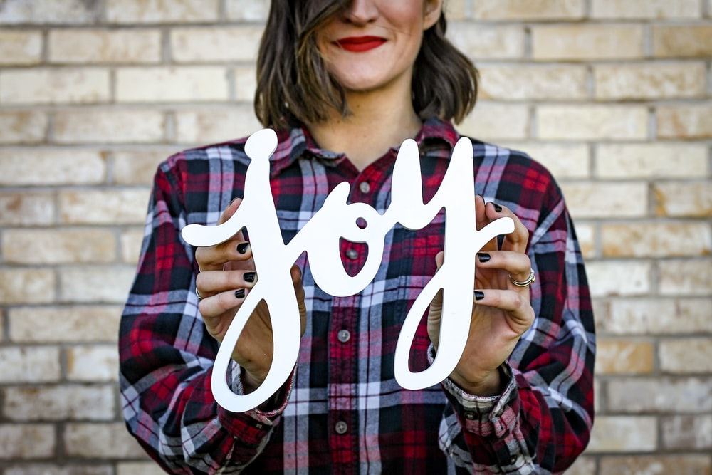 woman holding joy text
