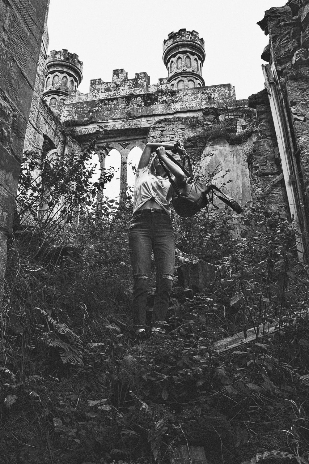 woman holding backpack near ruins