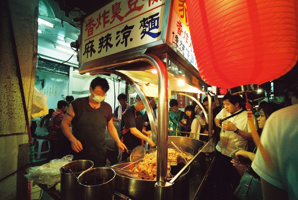 man wearing black apron and mask cooking food in street food area