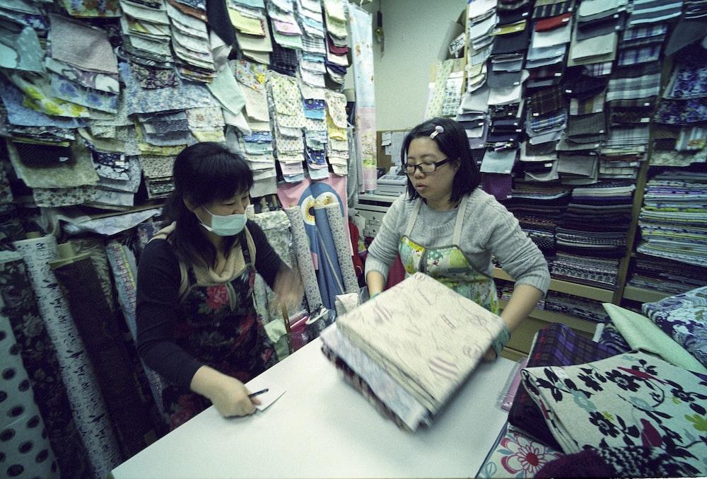 two women holding textiles