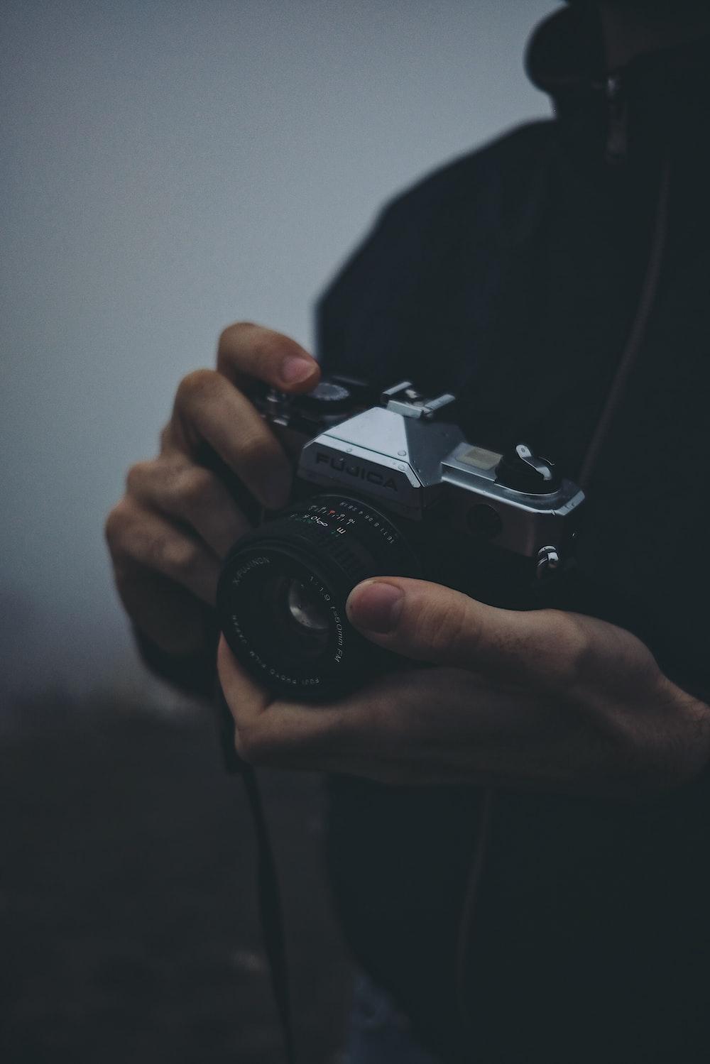 person holding black Fujica camera