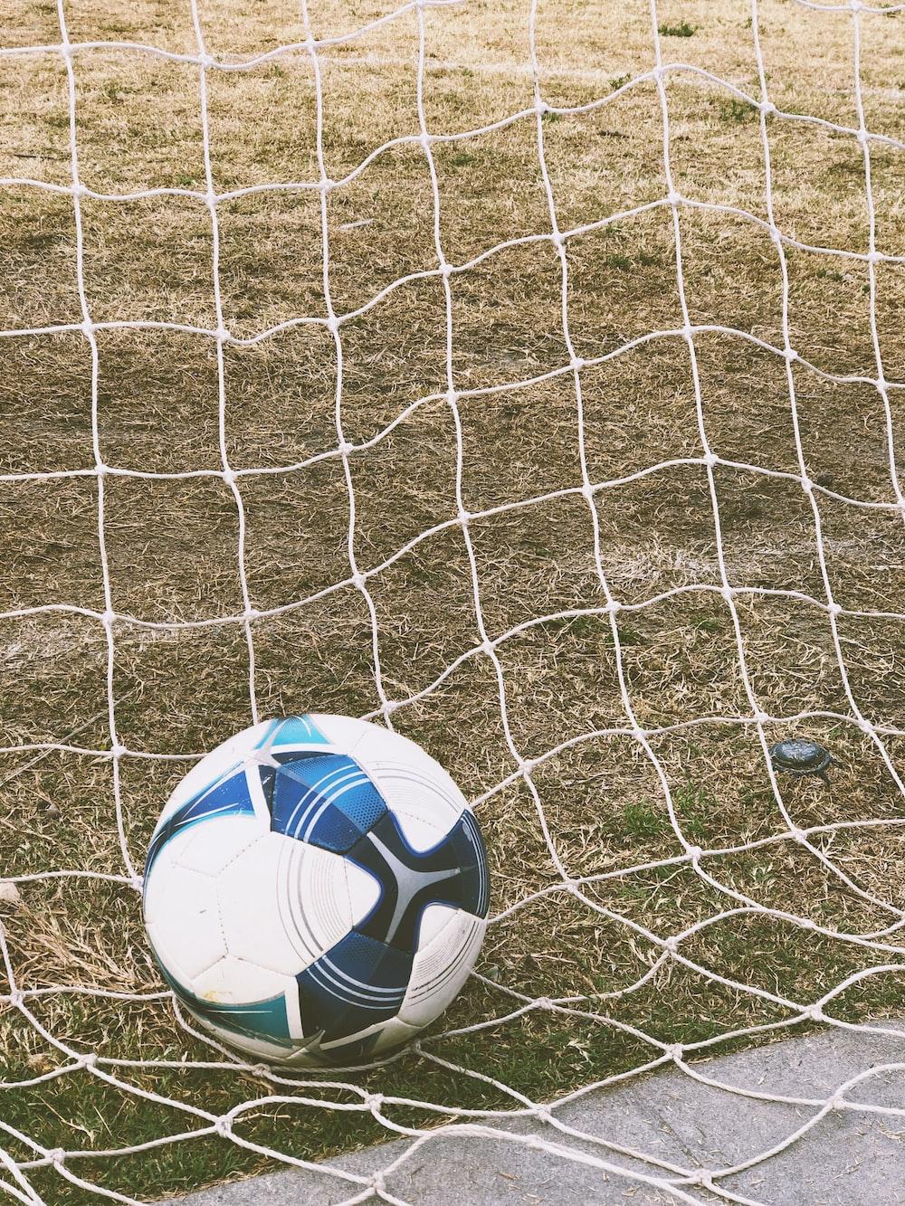 white and blue soccer ball on ground inside goal