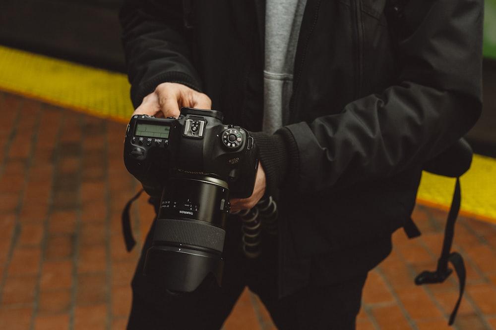 man using a black DLSR camera