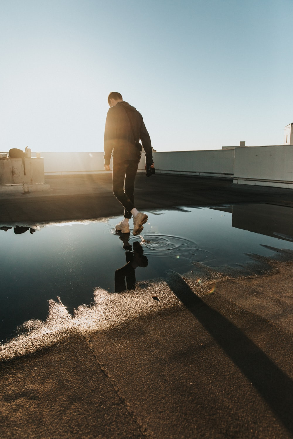 man walking on water puddle