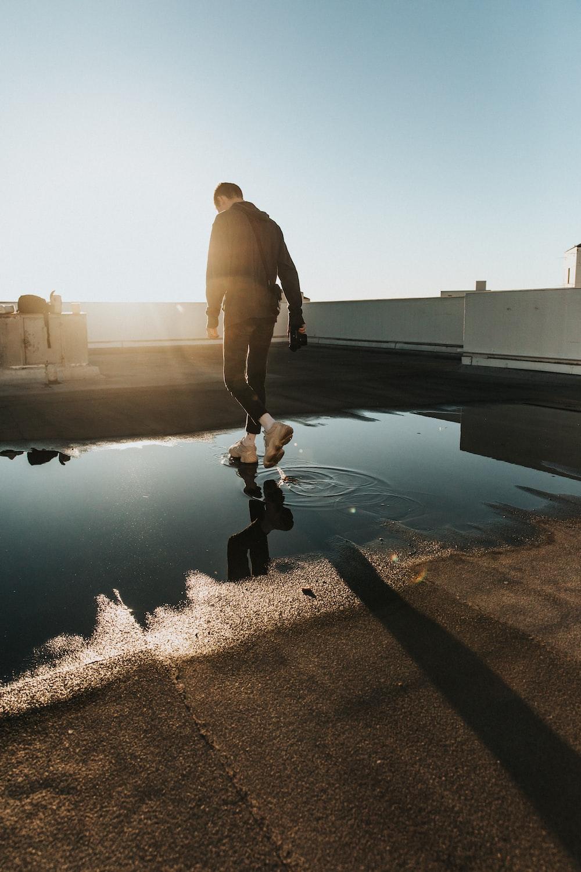 man walking on water puddle