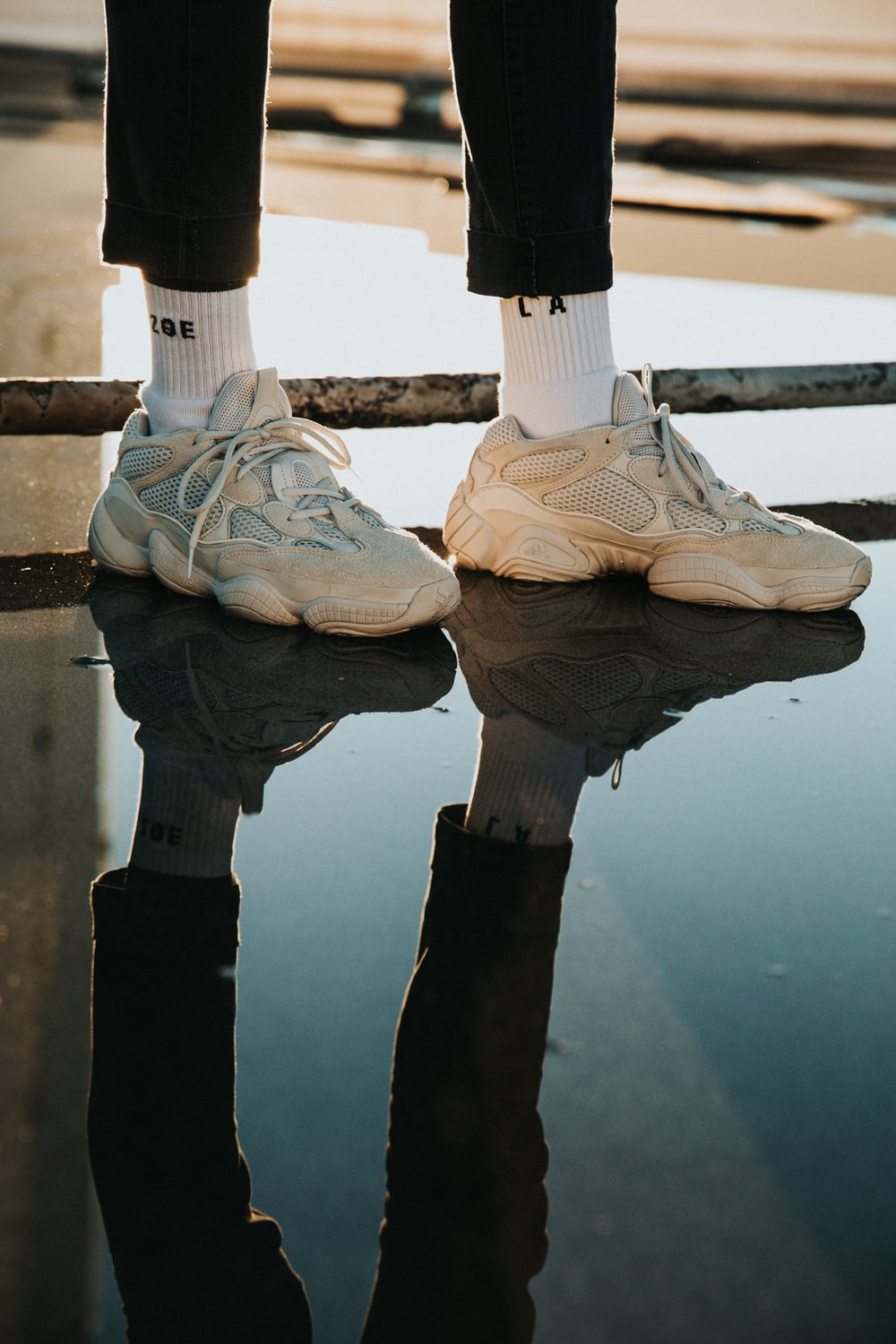 person wearing pair of white lace-up sneakers with reflection to water during daytime