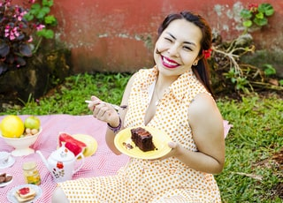 woman in polka-dot dress holding fork and plate with slice of cake