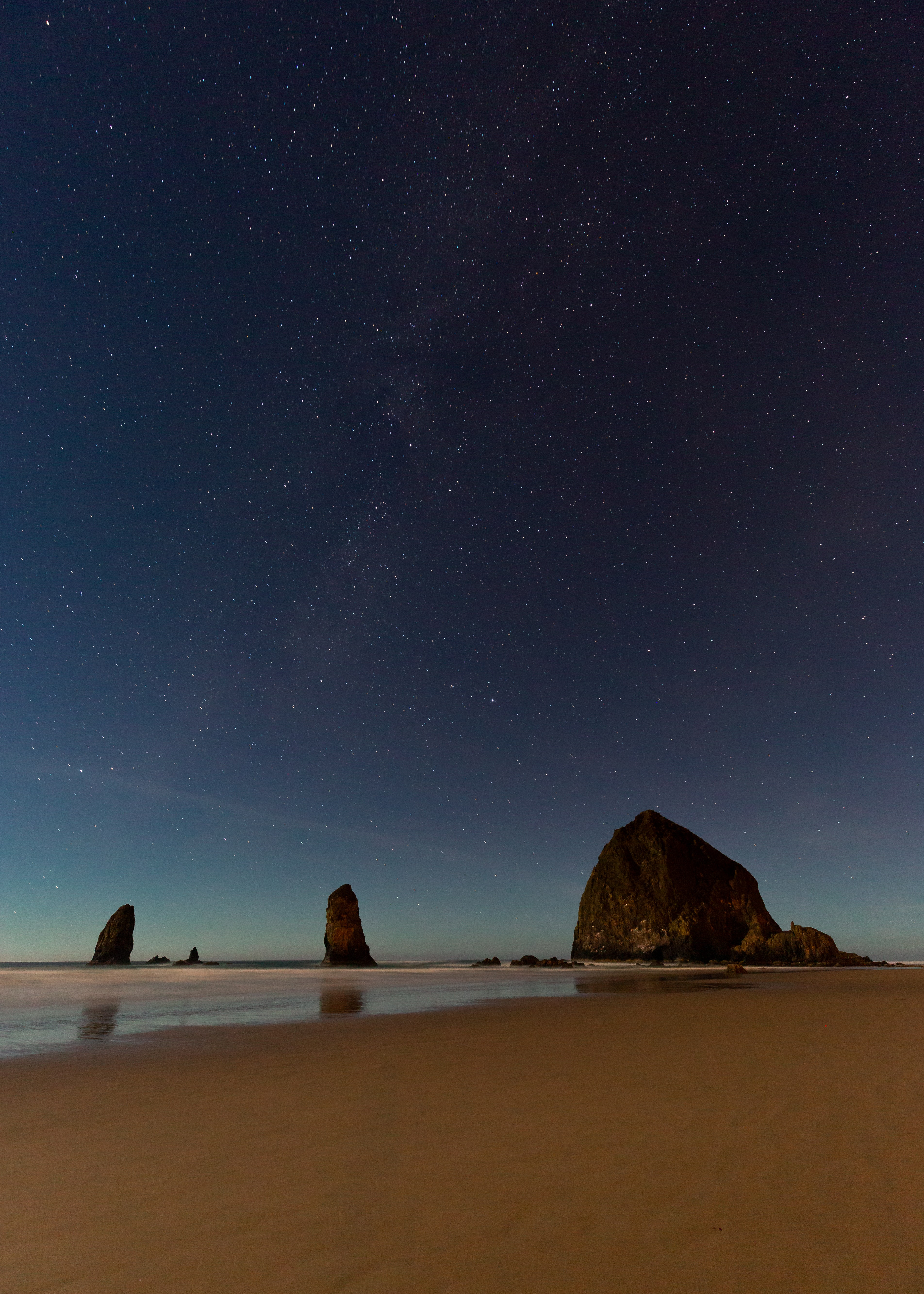rock formation near shore under starry sky