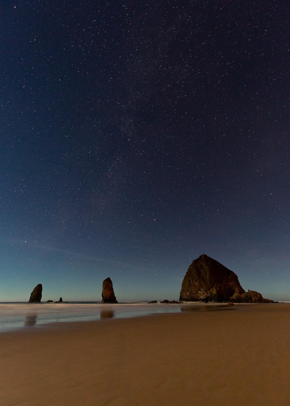 rock formation near shore under starry sky