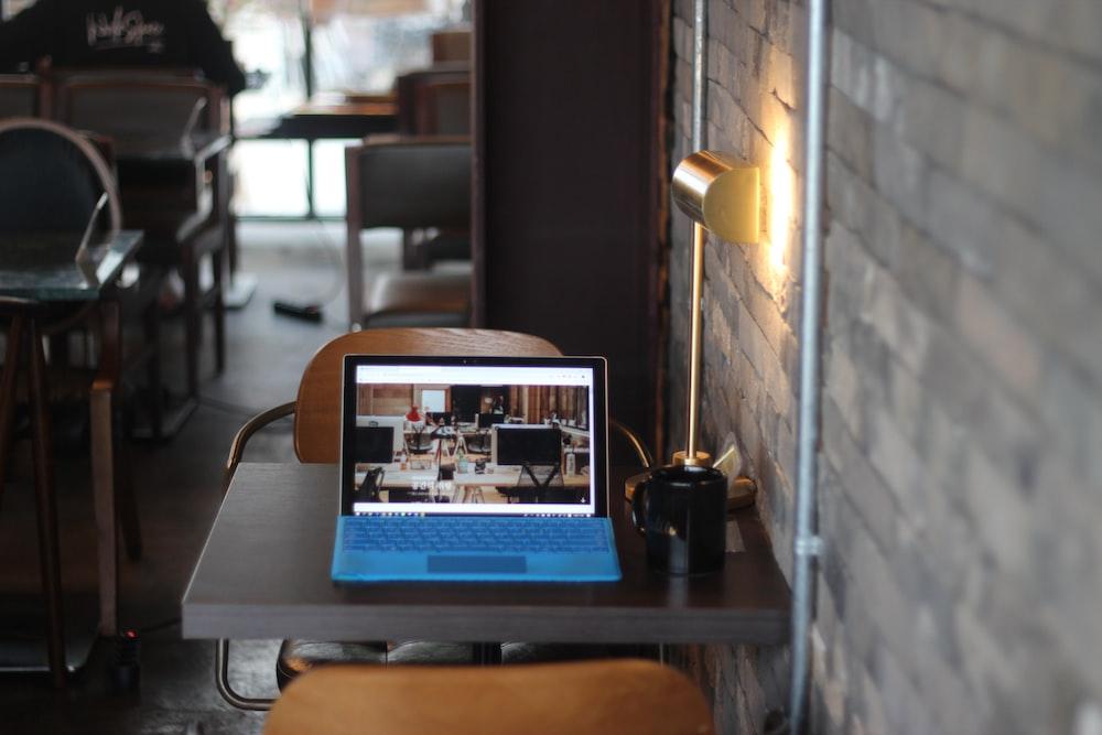 turned-on blue-and-black laptop computer on table near black ceramic mug