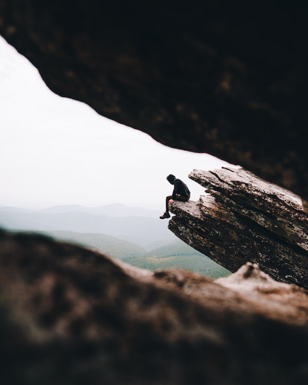 selective focus photography of person sitting on cliff during daytime