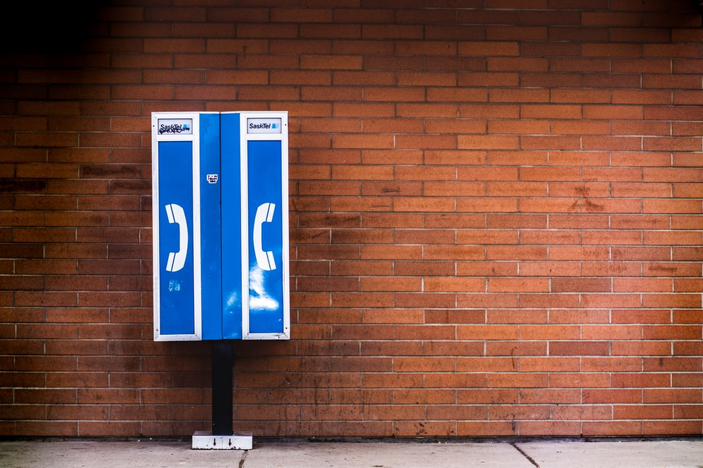 blue and white payphone near brown brick wall