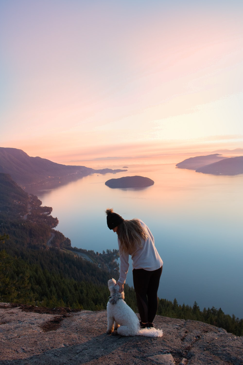 woman standing beside dog near the body of water