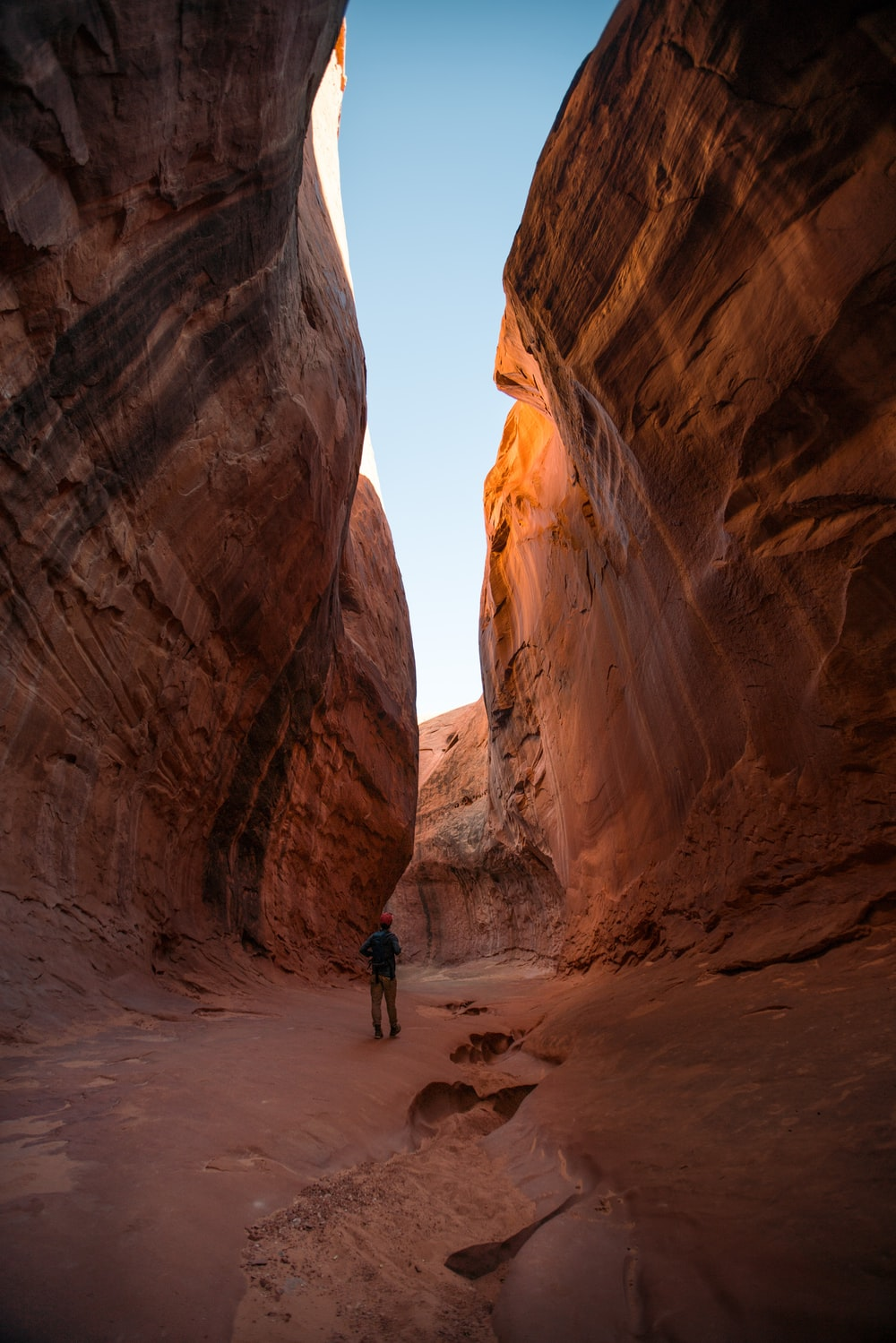 man standing in middle of rock formation during daytime