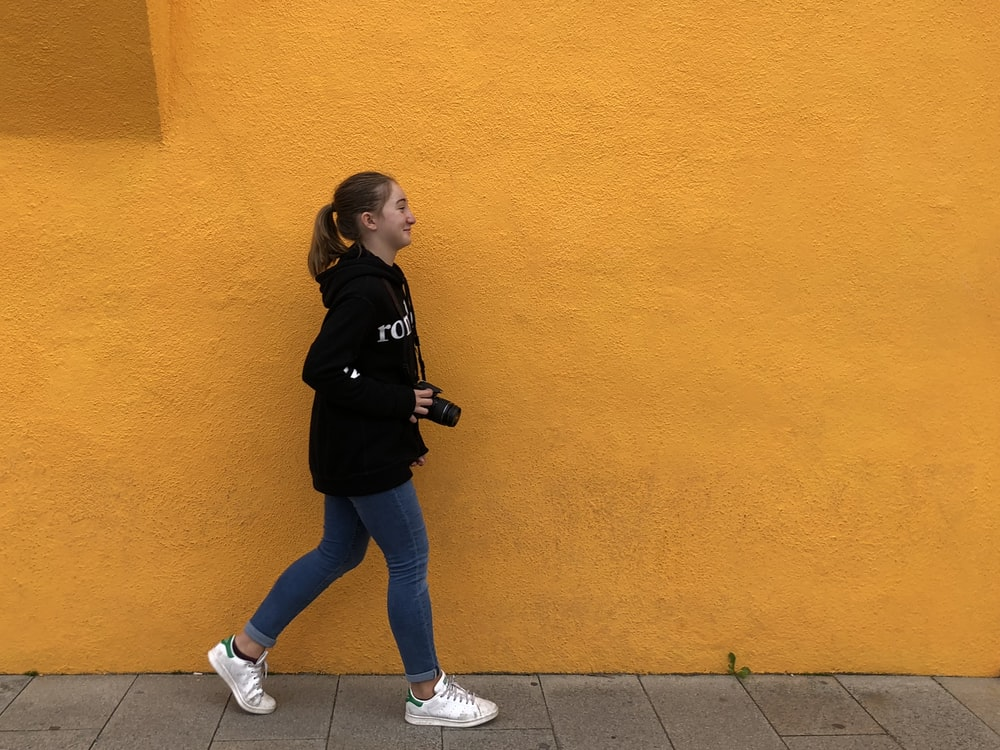 girl walking on sidewalk