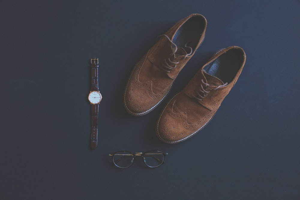 pair of brown suede oxford wingtip shoes beside black framed eyeglasses and round gold-colored and white analog watch with brown leather strap