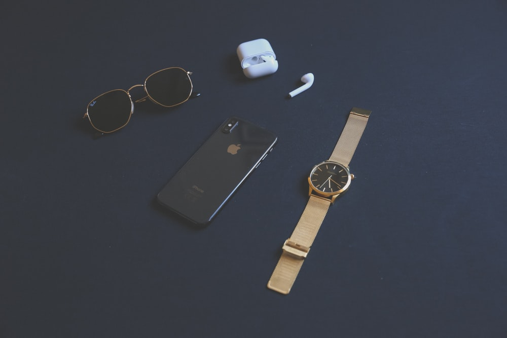 space gray iPhone X beside AirPods with case, round gold-colored analog watch and black sunglasses