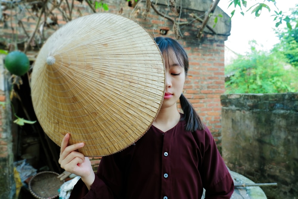 woman closing her eyes while holding straw hat