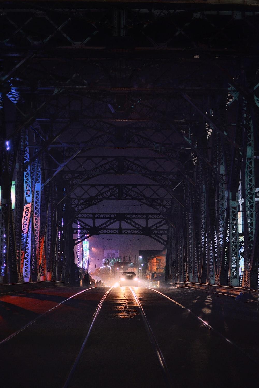 car on road under bridge at nighttime