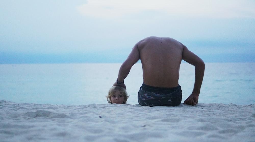 man sitting on seashore