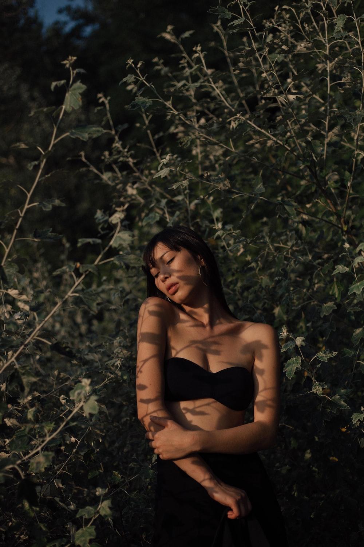 woman wearing a black bra at a grassy field
