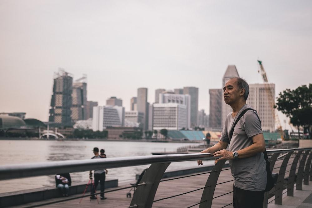 man leaning on metal railing during daytime