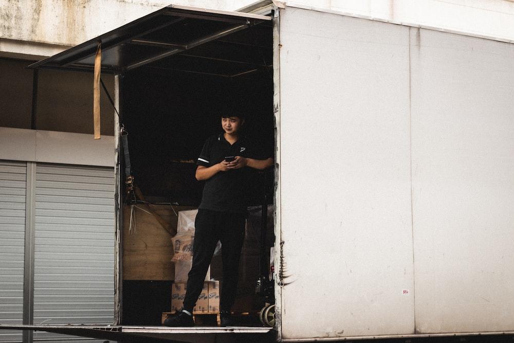 man inside a van wearing black shirt and pants