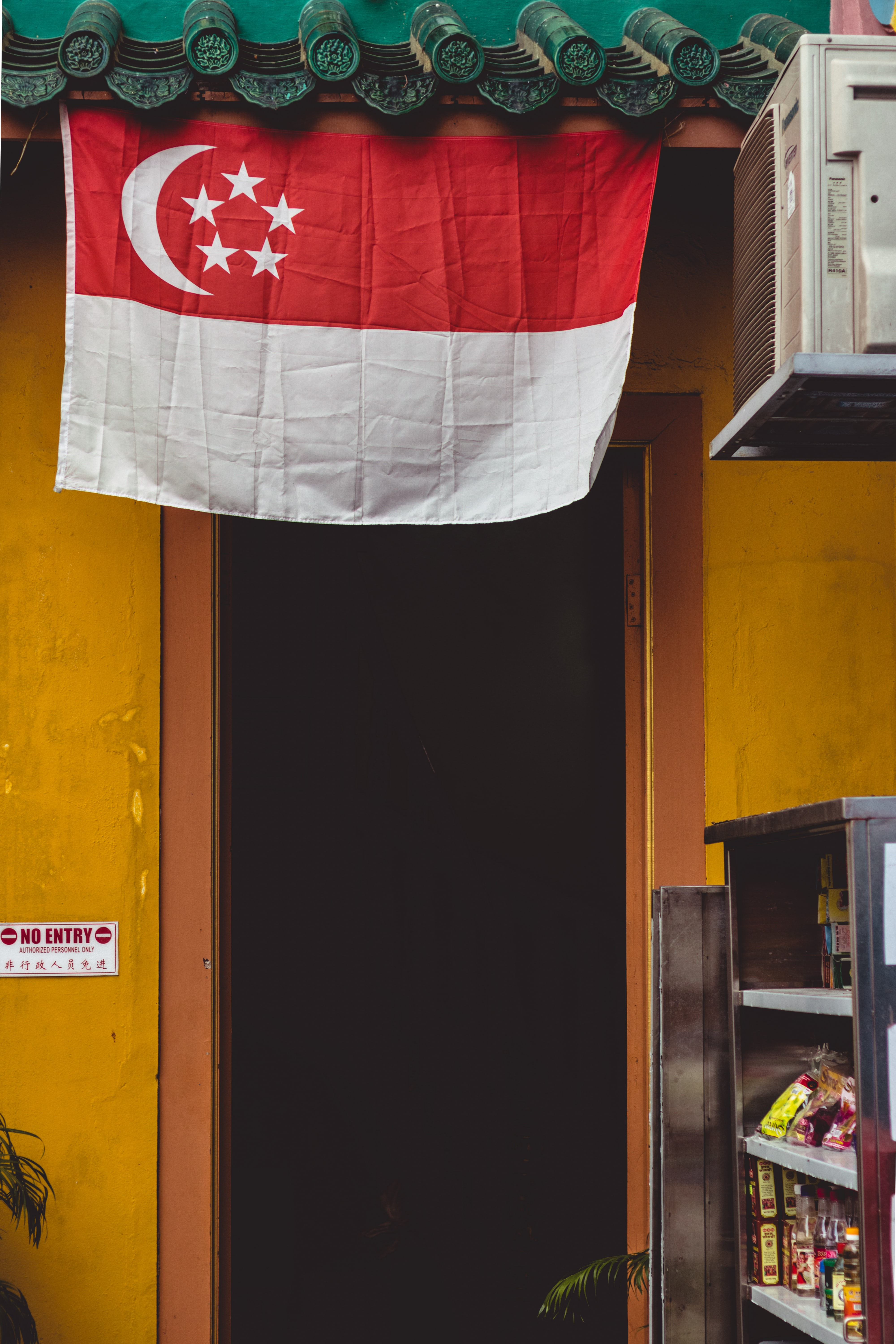 Singapore flag hung over a traditional building.