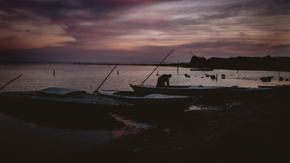 silhouette of man near boat on shore during dusk