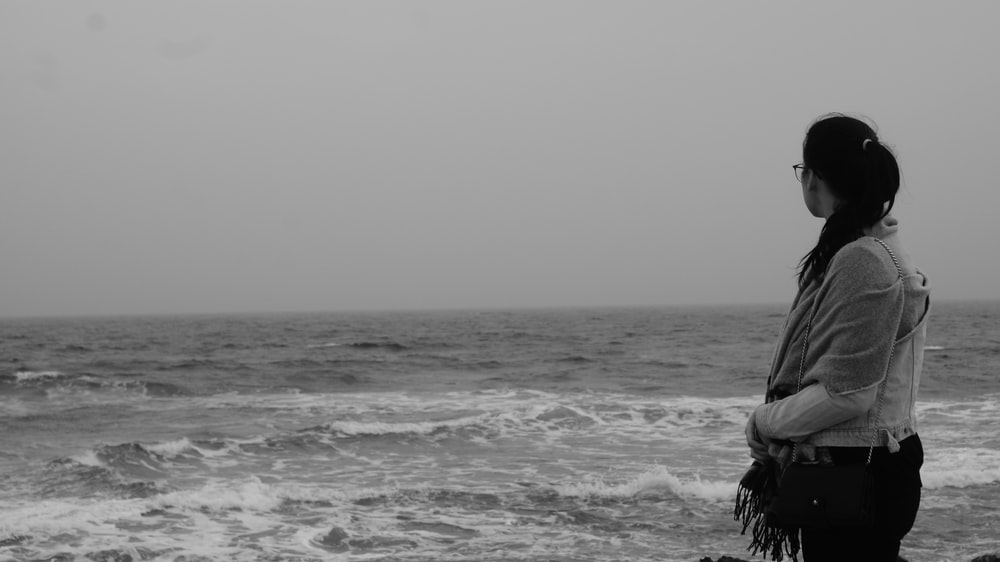standing woman near sea during daytime