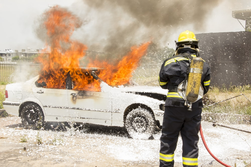 firefighter fighting burning car