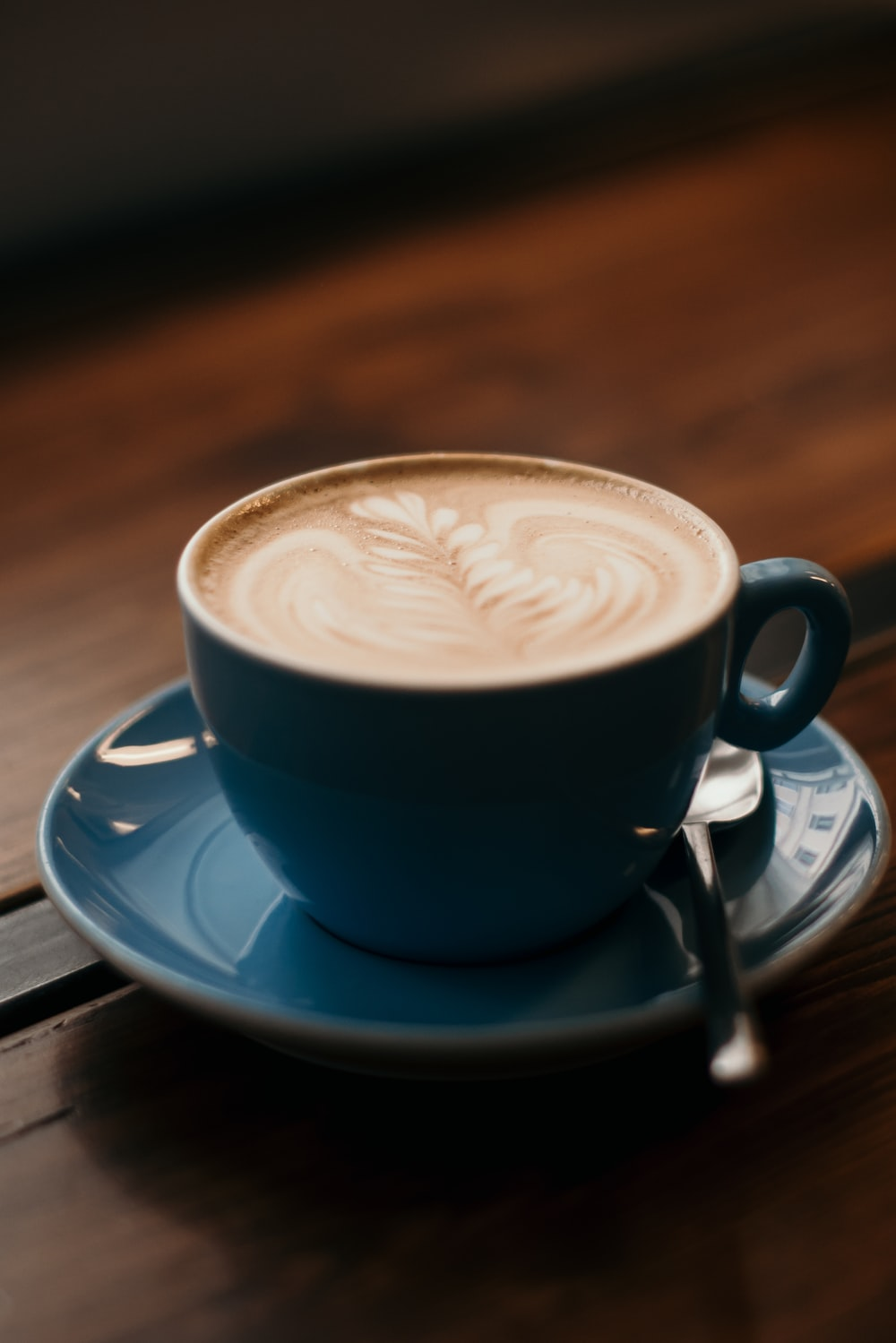 blue ceramic teacup set filled with cappuccino on table