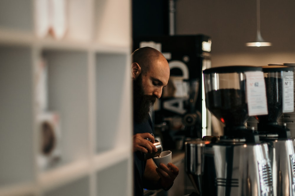 man pouring coffee on teacup