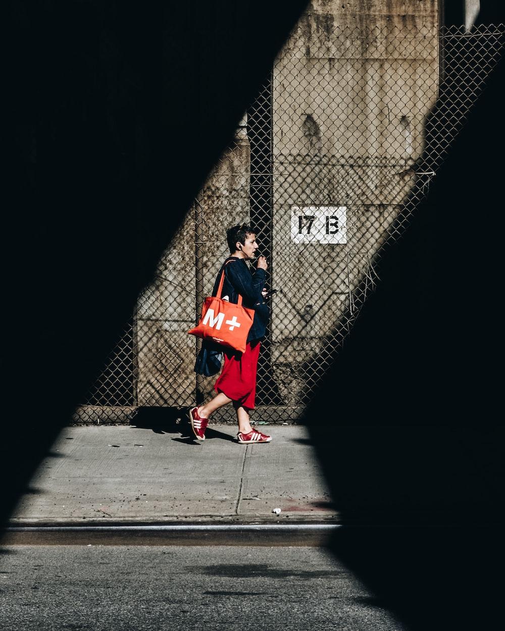 man walking carrying bag