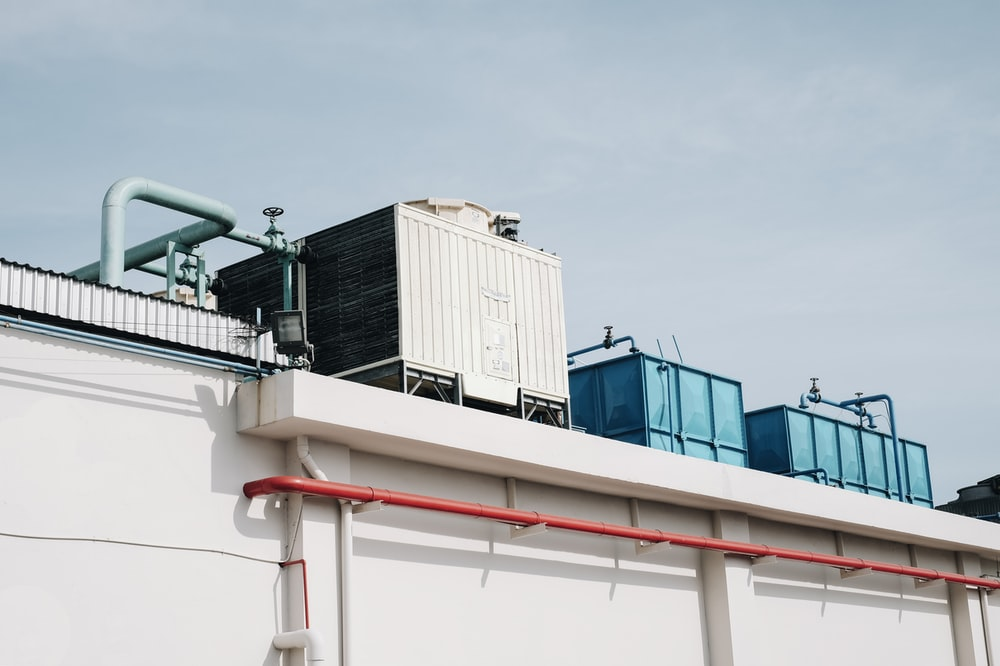 white and black standby generator on top of white concrete building