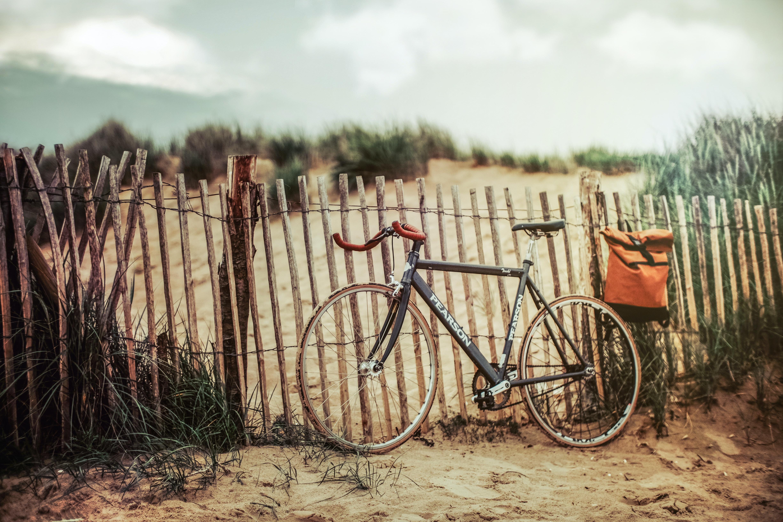 black road bike near brown wooden fence
