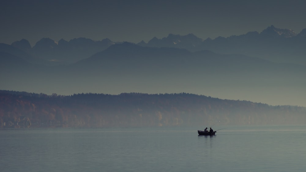 silhouette photography of person riding boat on body of water