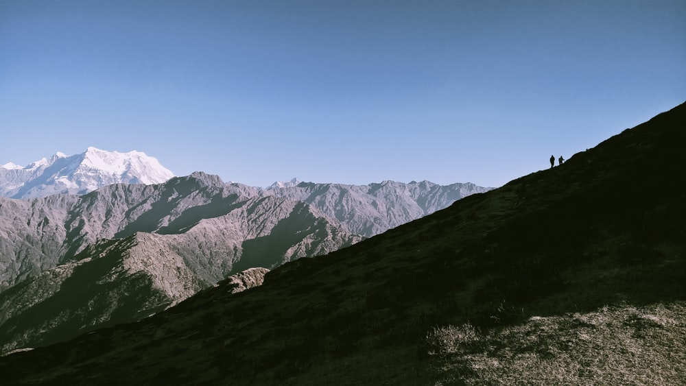 two person standing in mountain during daytime