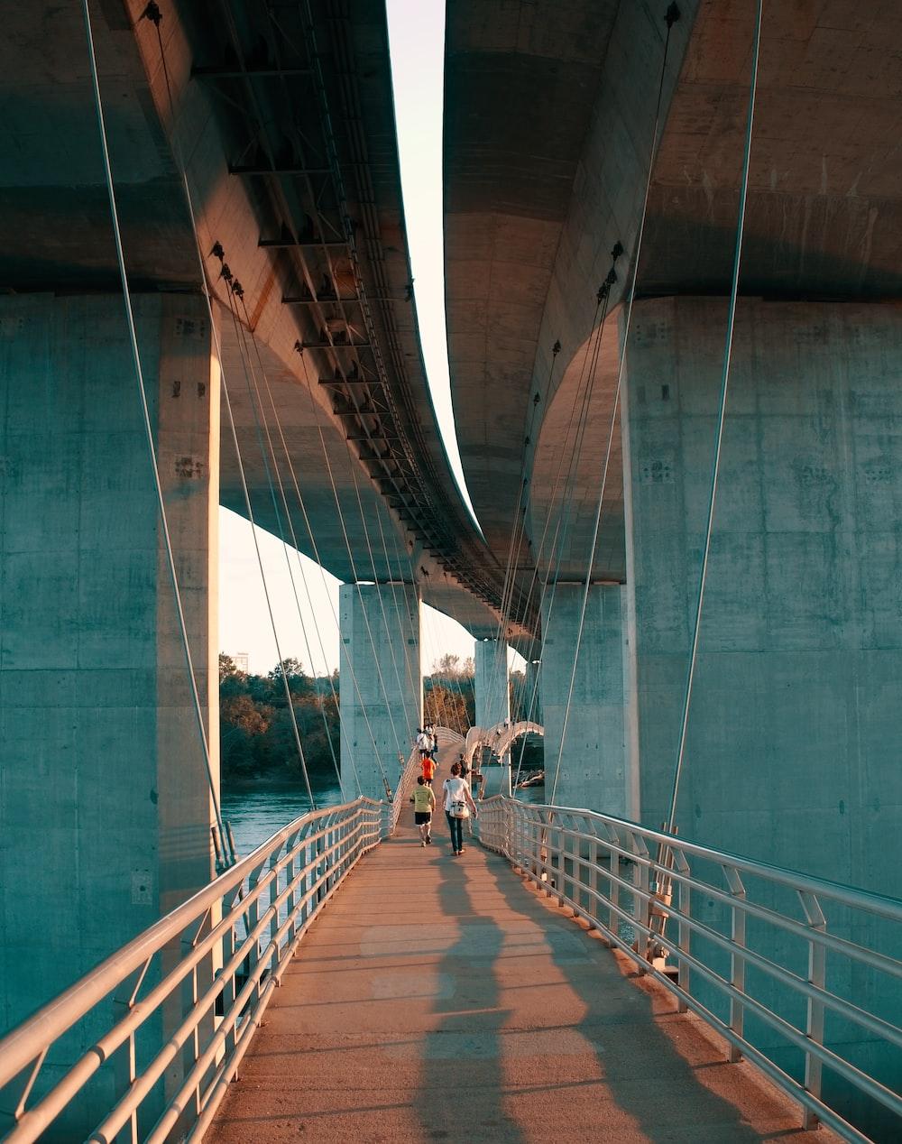 people walking on walk bridge during daytime