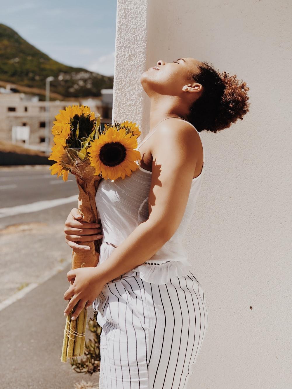 woman holding sunflower in vase