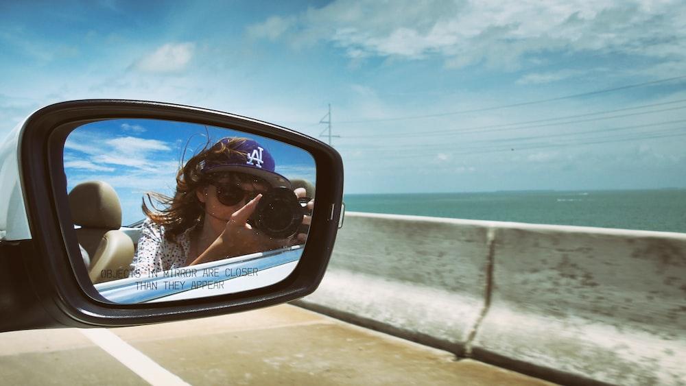 woman taking mirror shot selfie outdoor