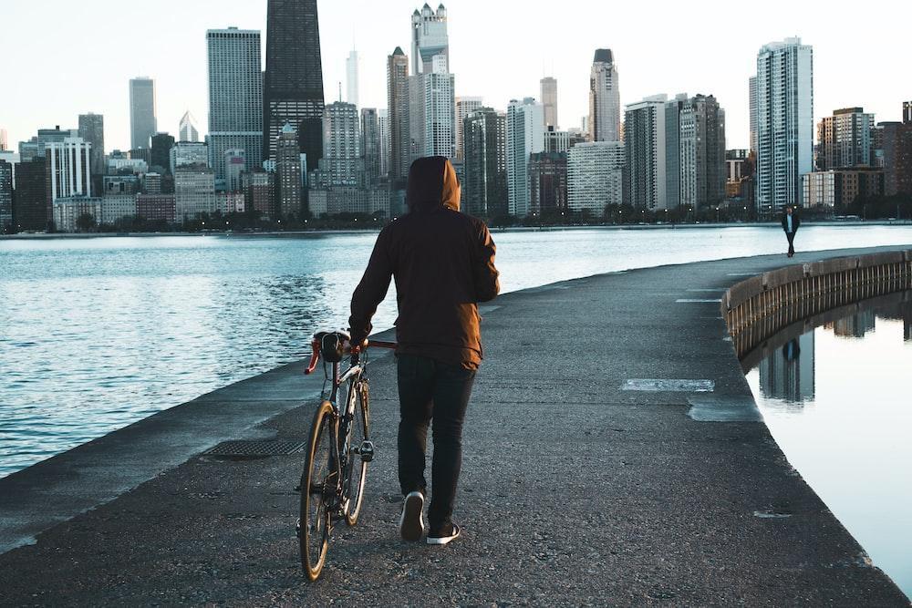 man walking on concrete walkway beside sea