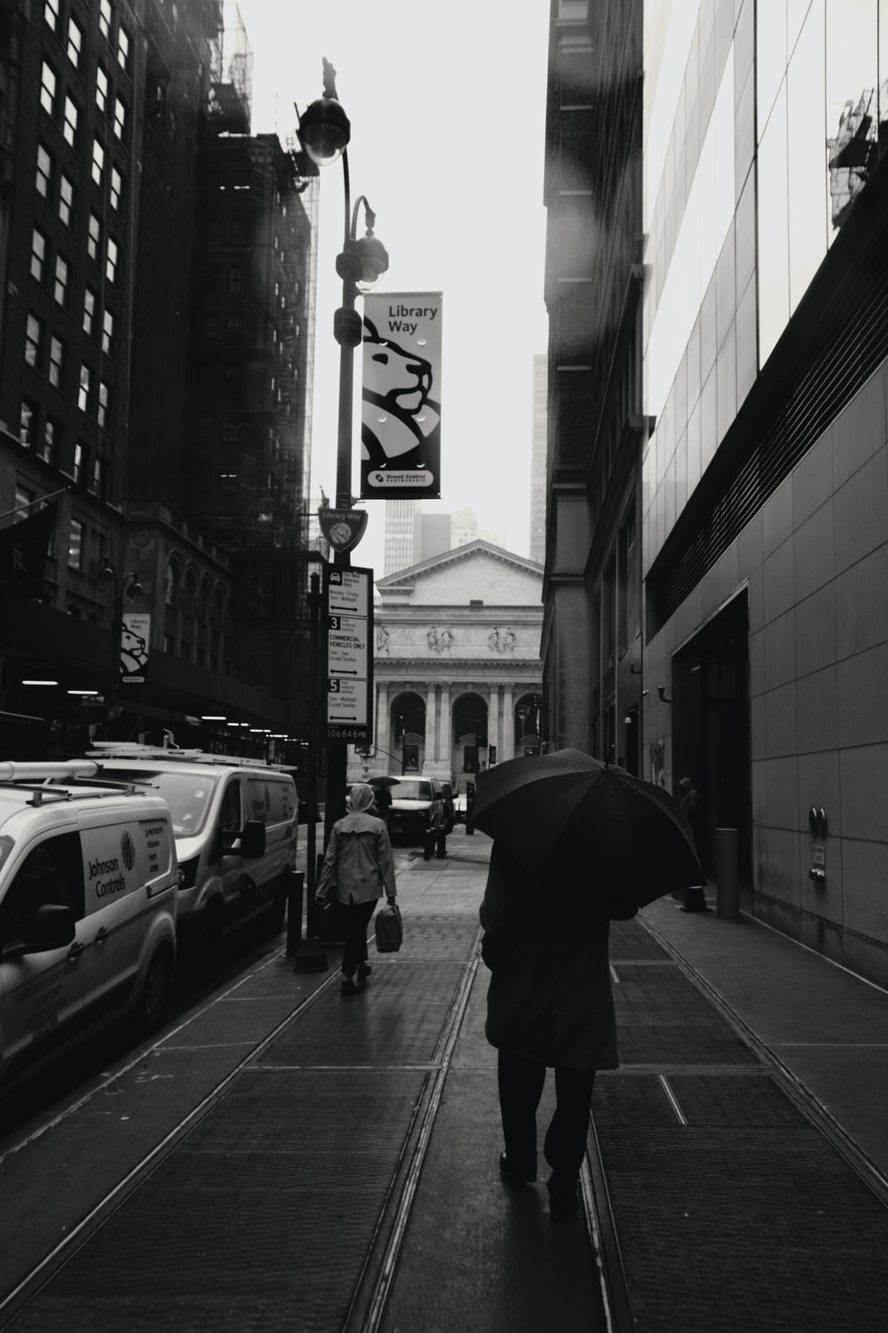 grayscale photo of person under umbrella walking on roadside