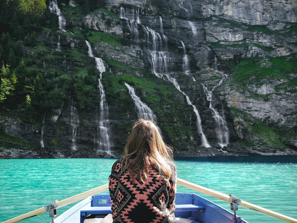 woman riding boat facing waterfalls