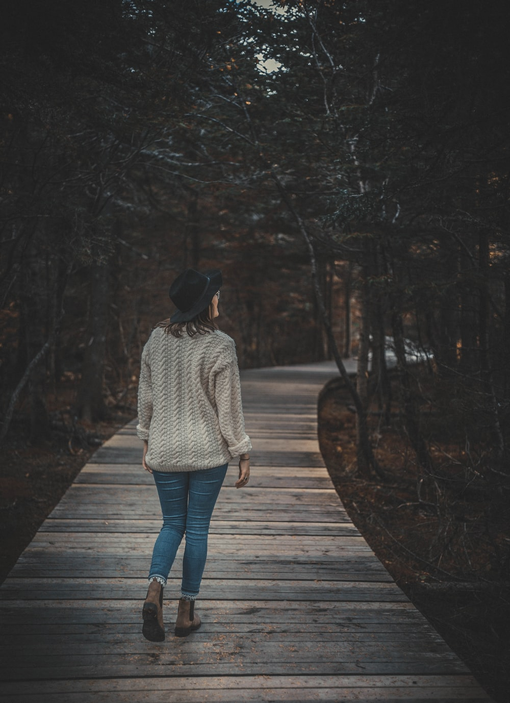 woman walking on wooden alley