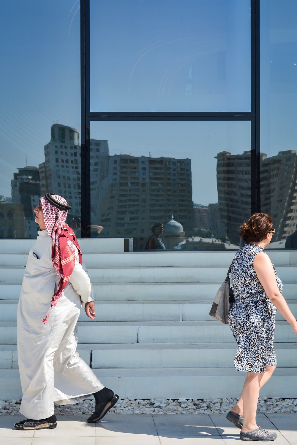 man and woman walking near glass building during daytime