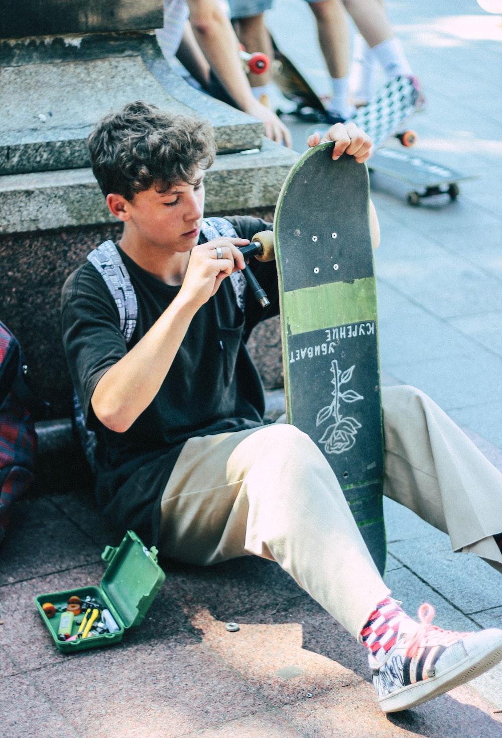 man fixing his skateboard