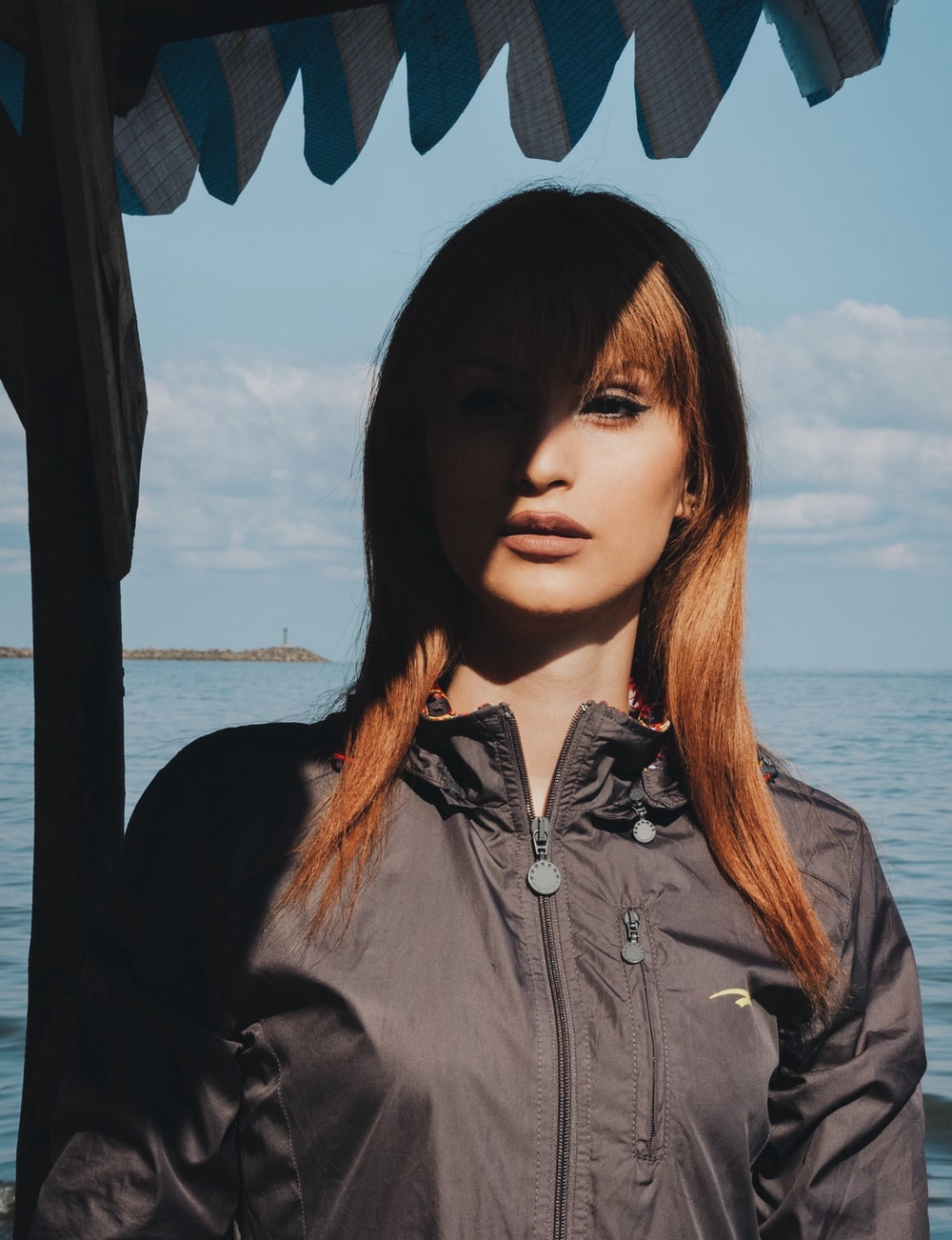 woman in black jacket standing on dock under cloudy sky during daytime