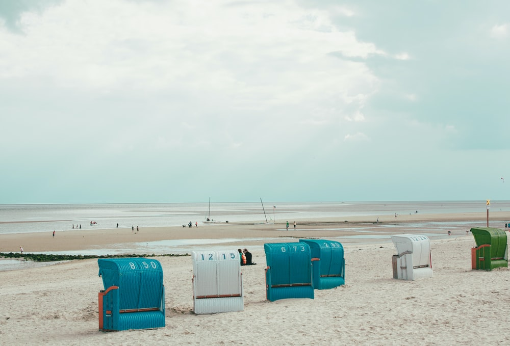 boxes on sand near shore under cloudy sky at daytime