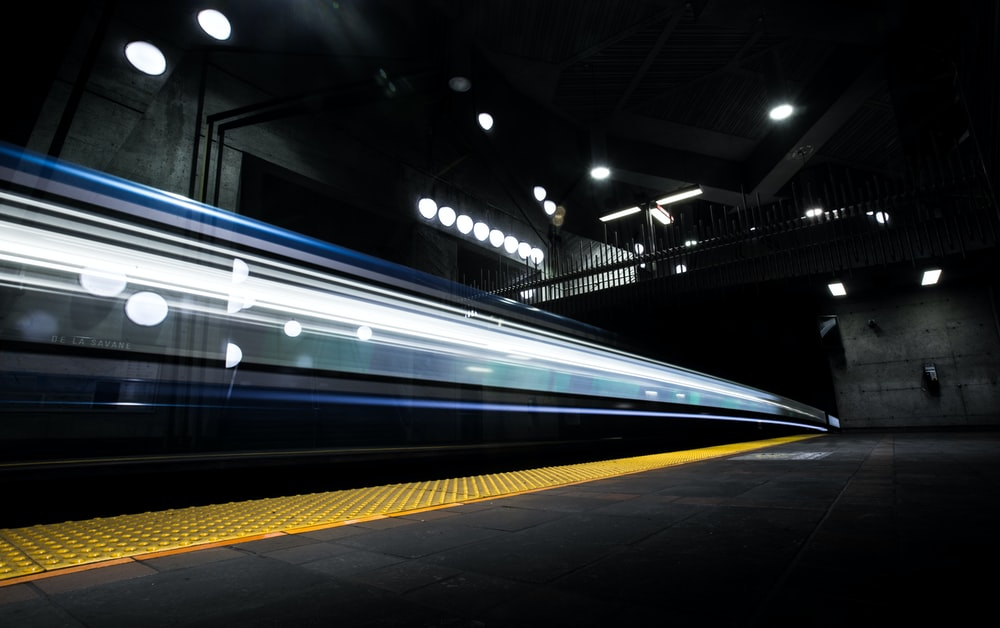 timelapse photography of train passing on track